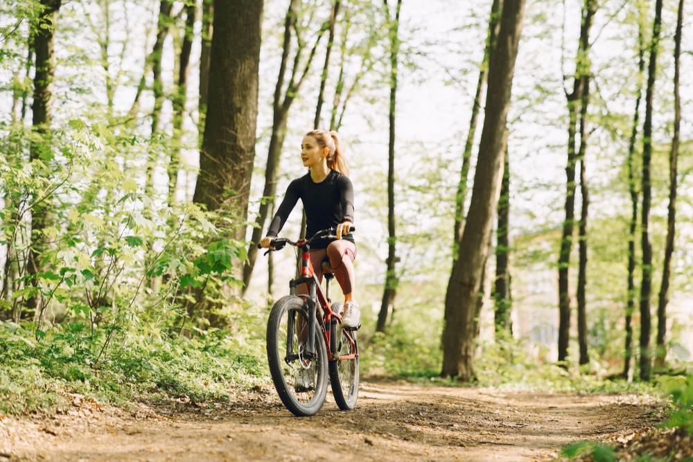 woman-riding-mountain-bike-forest