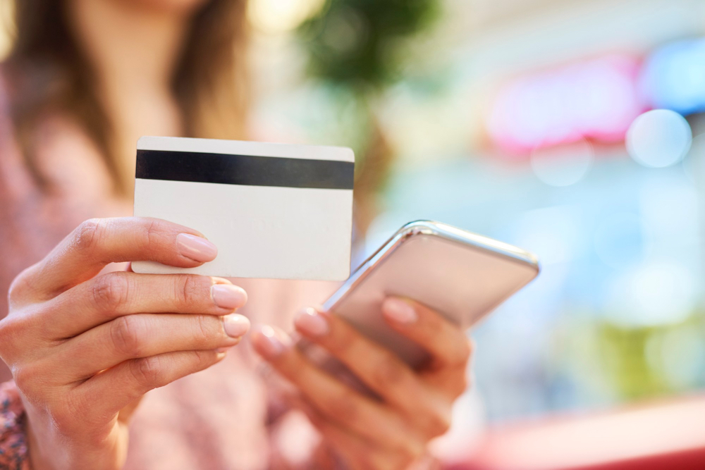 woman-using-mobile-phone-credit-card-during-online-shopping